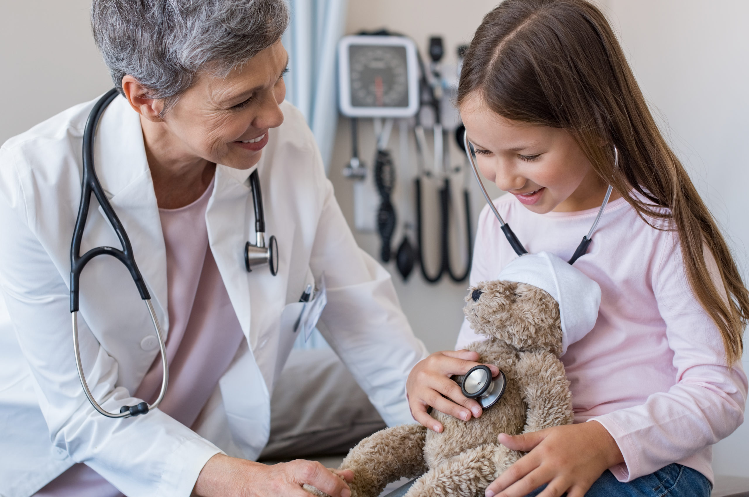 Doctor with a little girl and teddy bear
